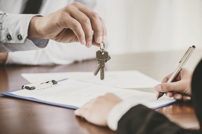 person handing keys over contract